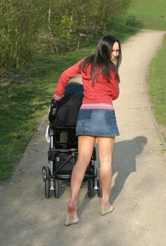 Cute brunette young mom walking in the..